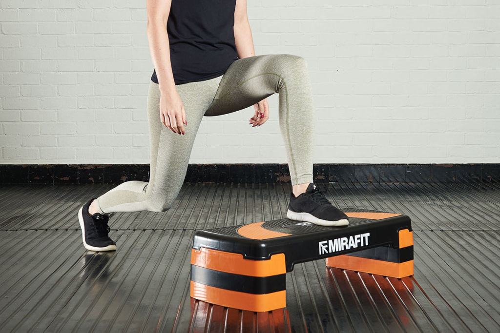 fitness expert doing lunges using a mirafit aerobic stepper