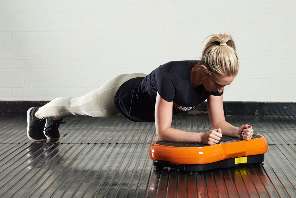 fitness expert does a plank on a mirafit vibration plate