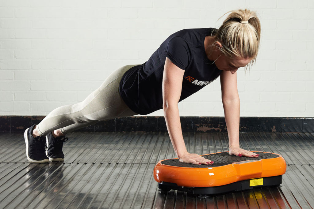 fitness expert does a push up on a mirafit vibration plate