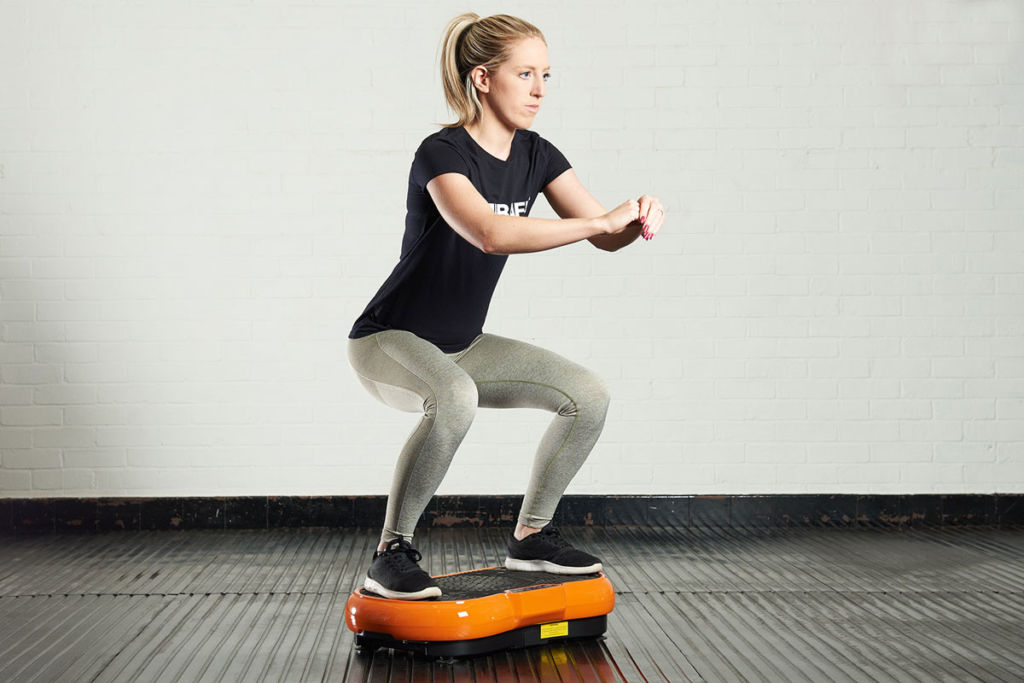 fitness expert does a squat on a mirafit vibration plate