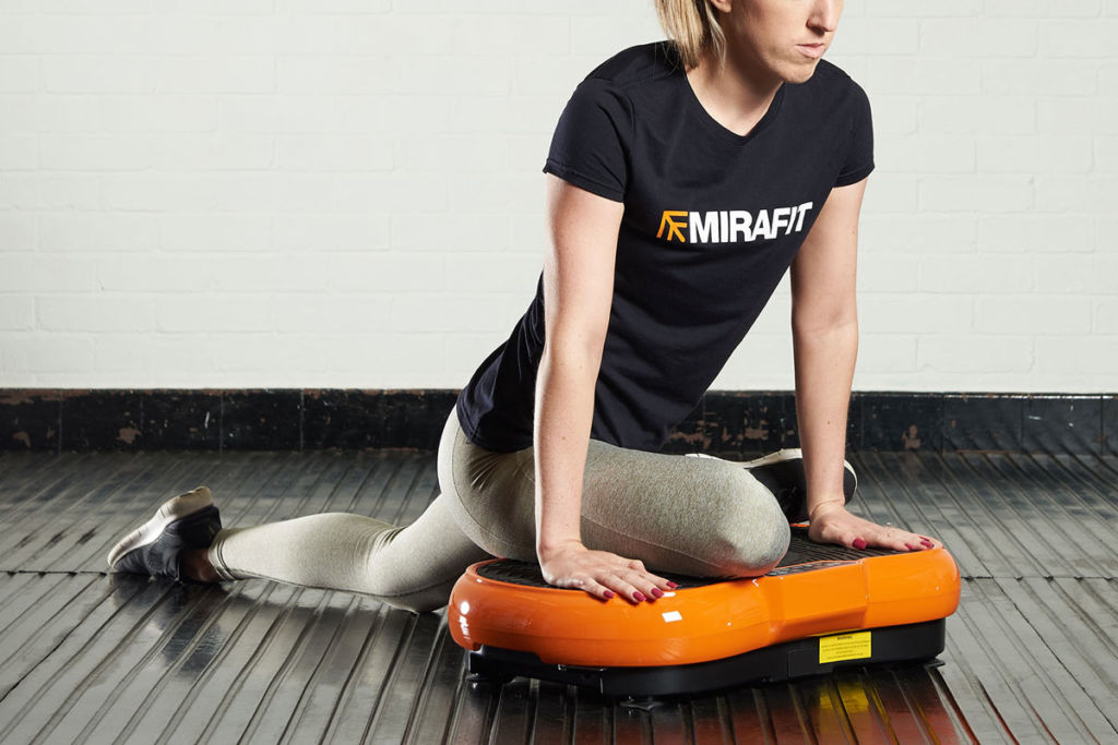 fitness expert does yoga pigeon pose on a mirafit vibration plate
