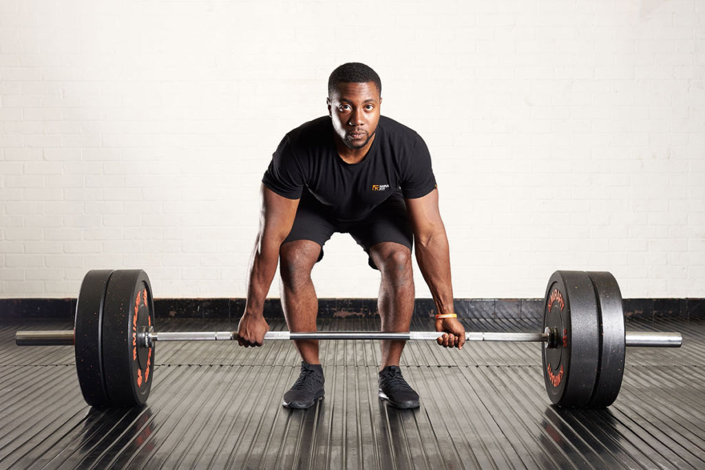 fitness expert performs a standard deadlift using mirafit gym equipment