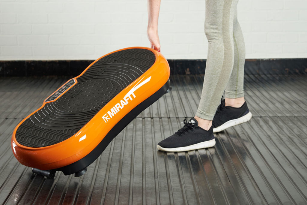 fitness expert putting a vibration plate on to a gym mat