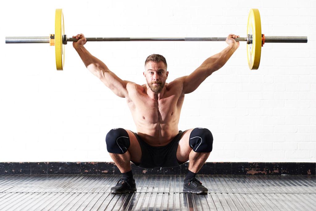 mirafit fitness expert does an overhead squat press