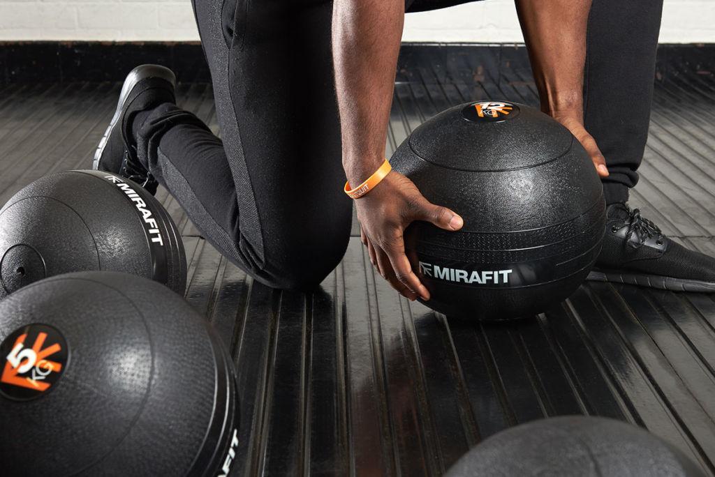 fitness expert using a mirafit slam ball