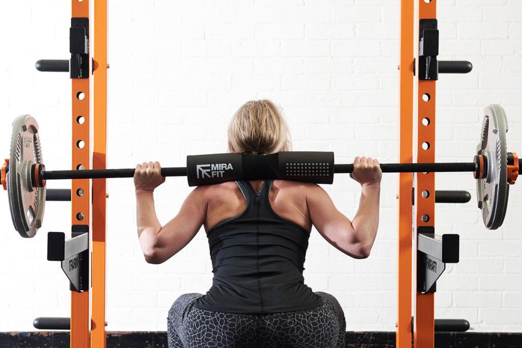 mirafit fitness expert squats using a power rack