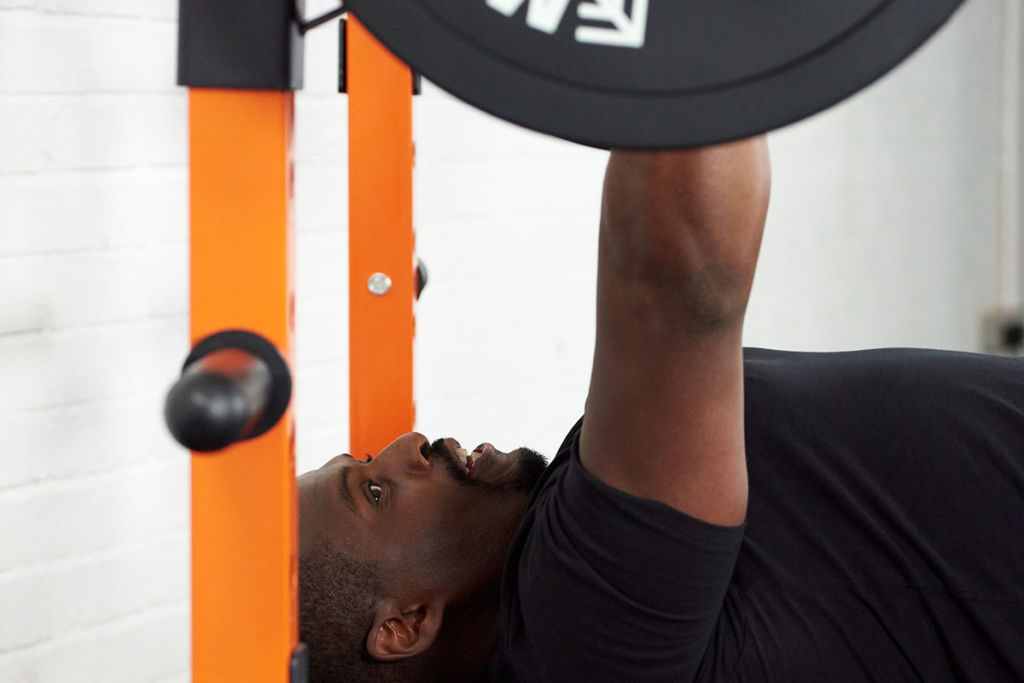 personal trainer uses mirafit power rack to bench press