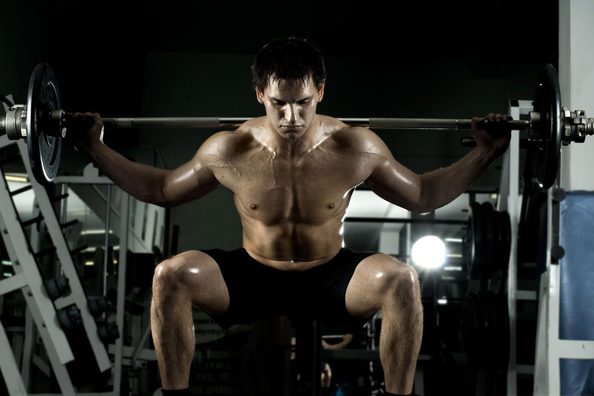 Strong Man doing squats on a squat rack
