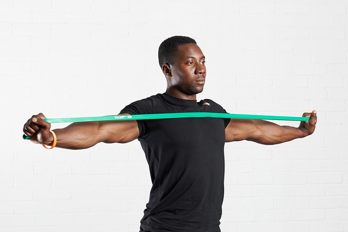 young man holding a green resistance band in his hands stretching it across his chest to exercise