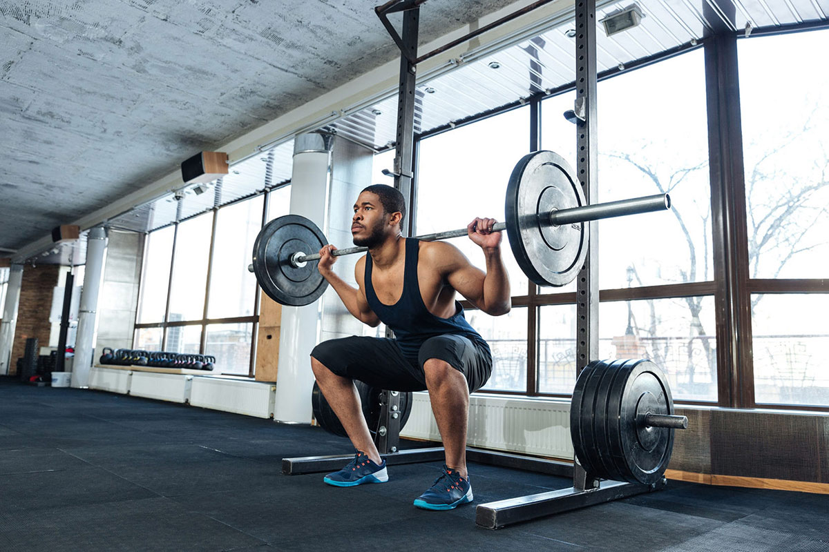 Fit-Man-In-Squatting-Position-Using-Squat-Rack-And-Weights