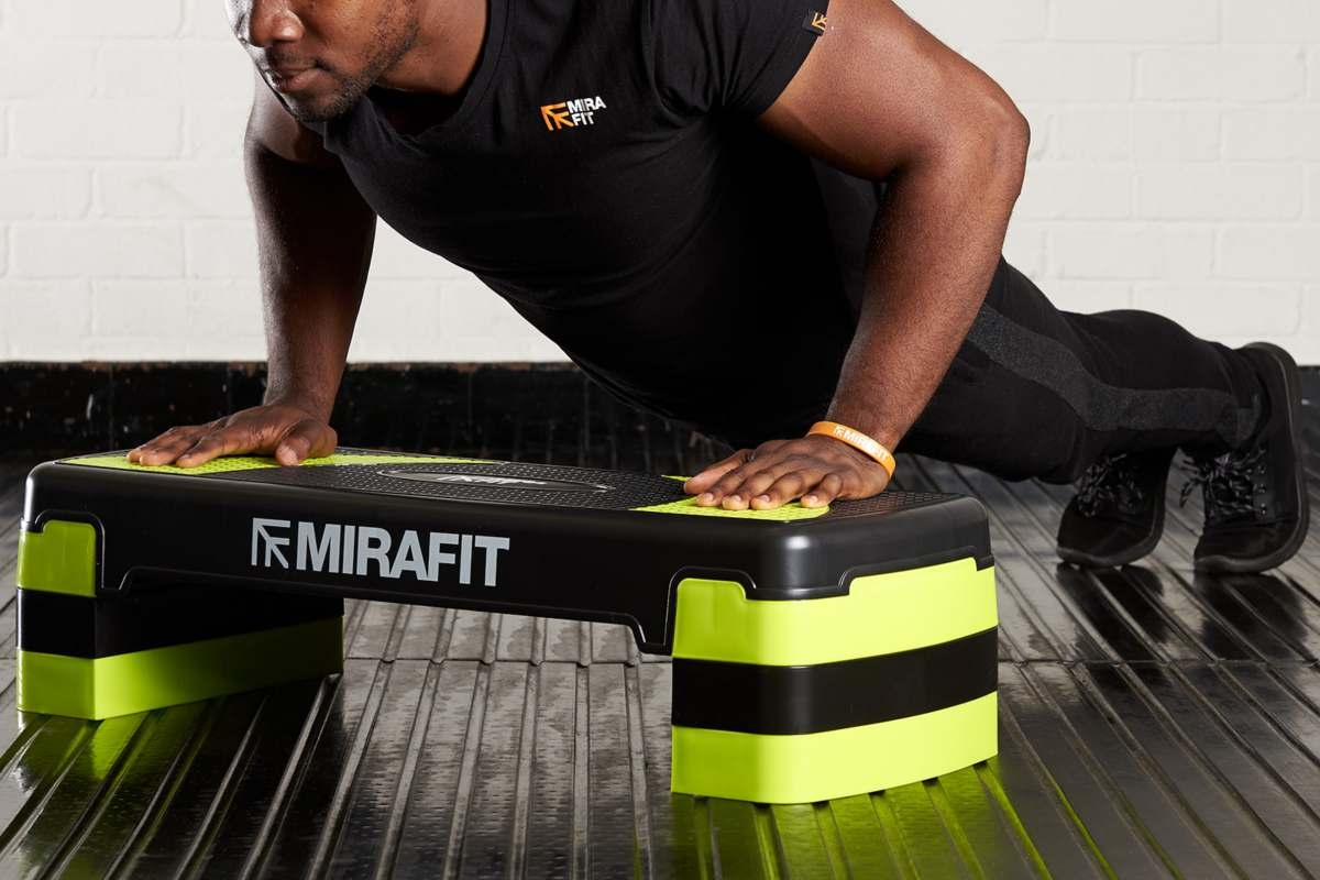 young healthy man doing a hiit workout using an exercise stepper doing a burpee