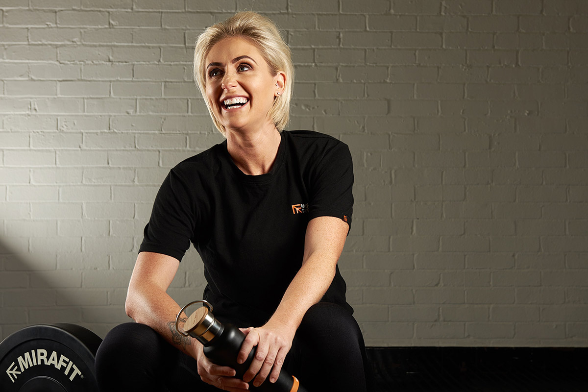 blonde woman laughing in the gym for a photoshoot