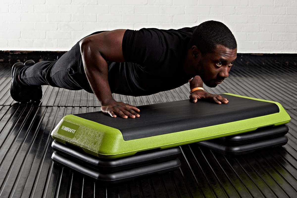 young man using a premium exercise stepper in his home gym