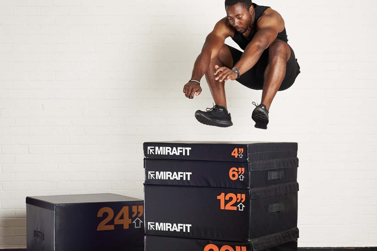 young healthy man jumping onto a stack of plyo boxes whilst doing a calorie burning exercise
