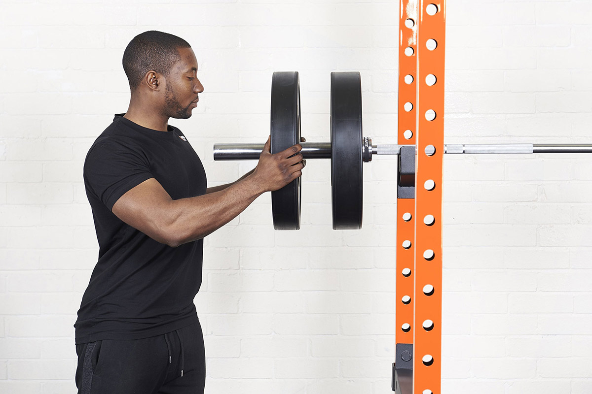 young man sliding black olympic weight plates onto a bar resting on a squat rack