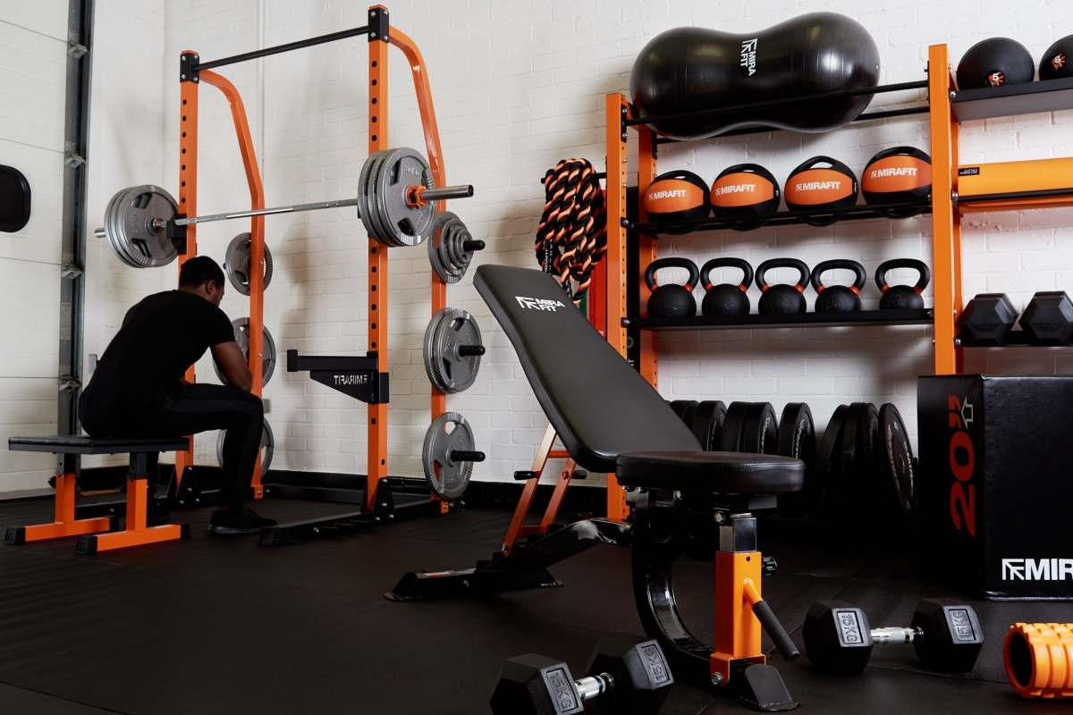 garage gym full of orange and black gym equipment including kettlebells medicine balls weight benches