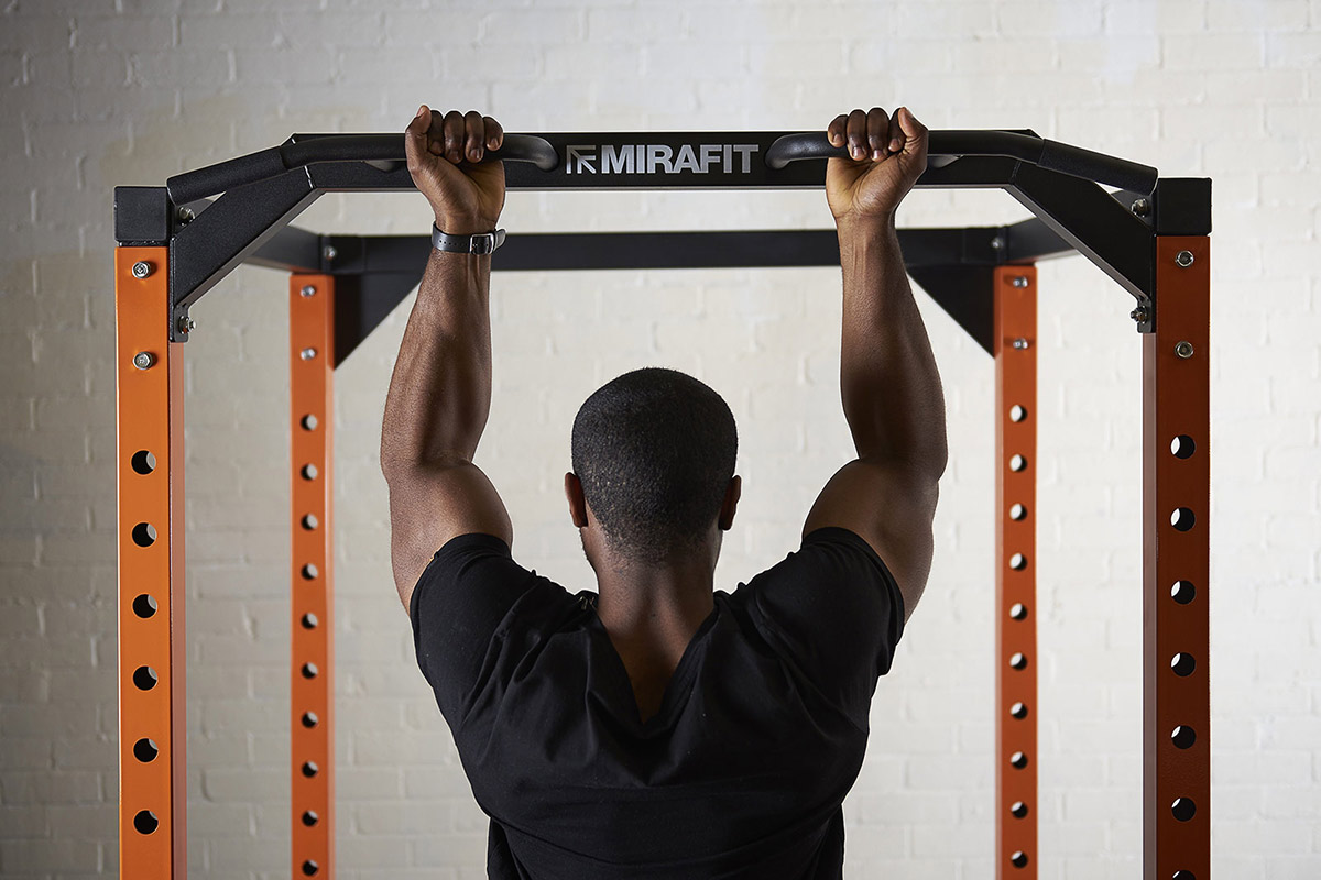 young man doing a chin up on a mirafit power cage