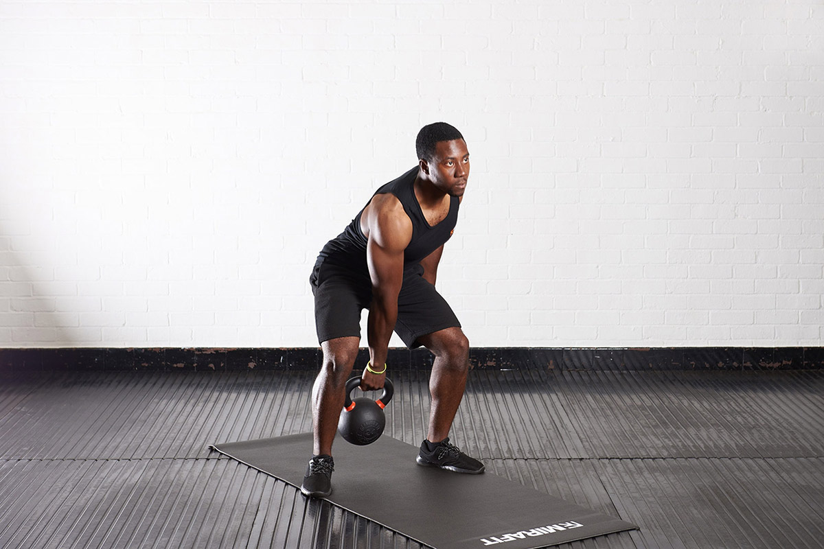 image of mirafit model using mirafit kettlebell to do a clean and press midway position