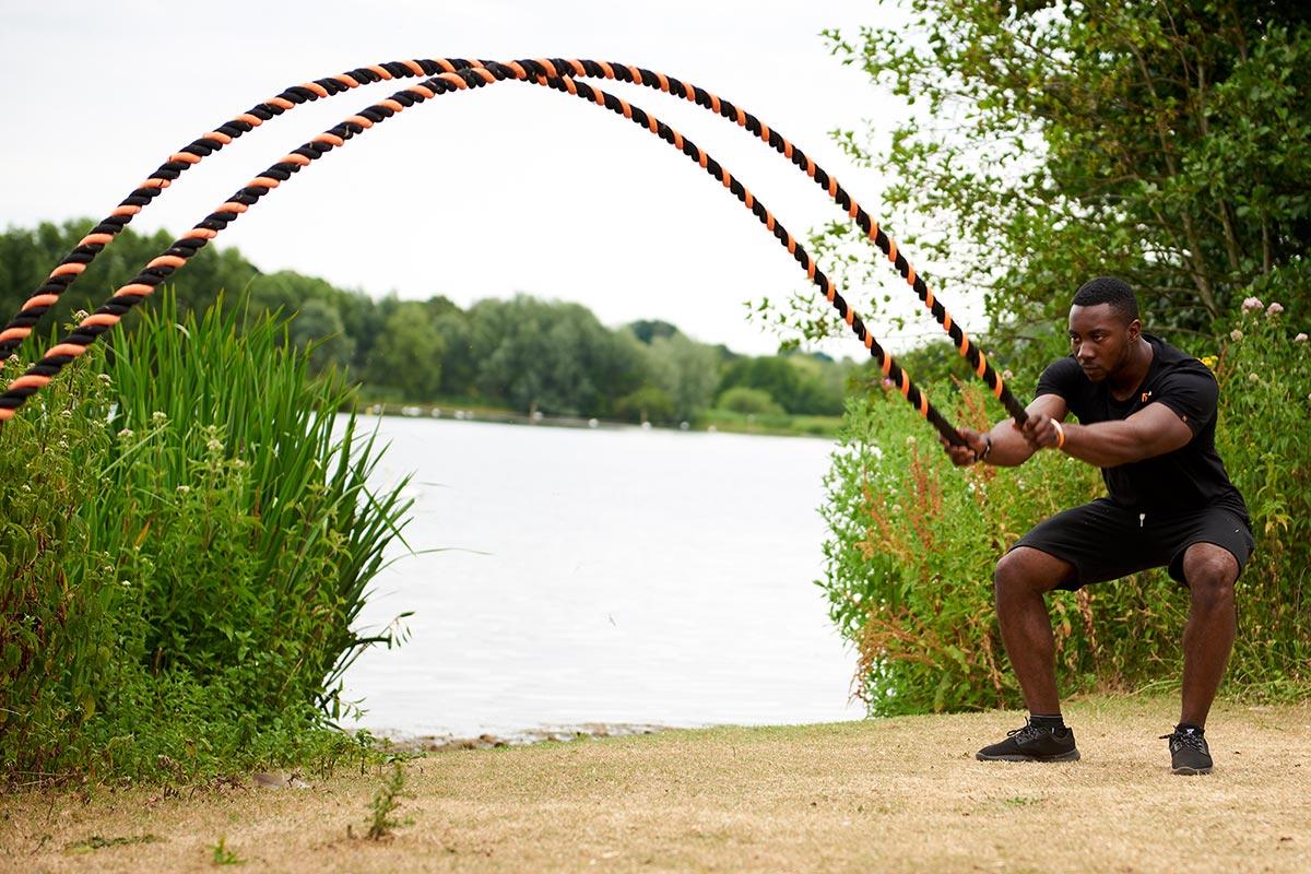 image of mirafit model using battle ropes outside