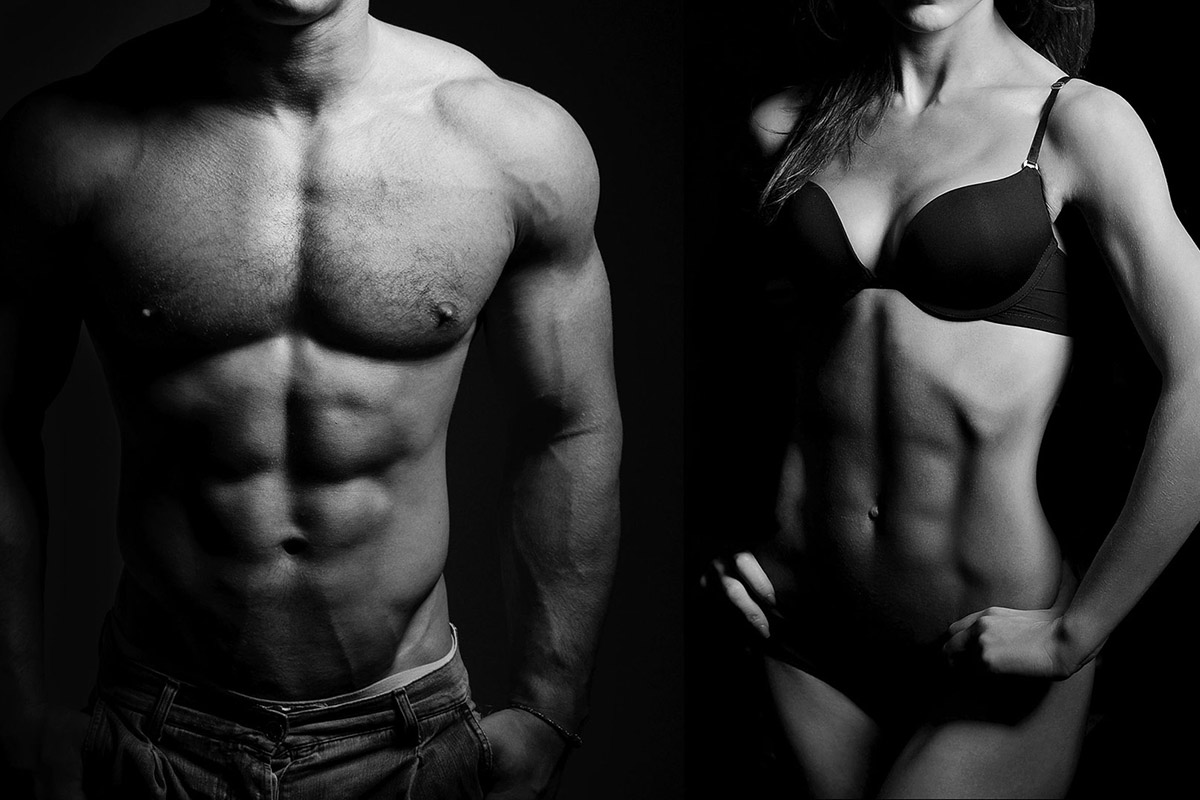Fit and muscly man and woman standing next to each other in black and white