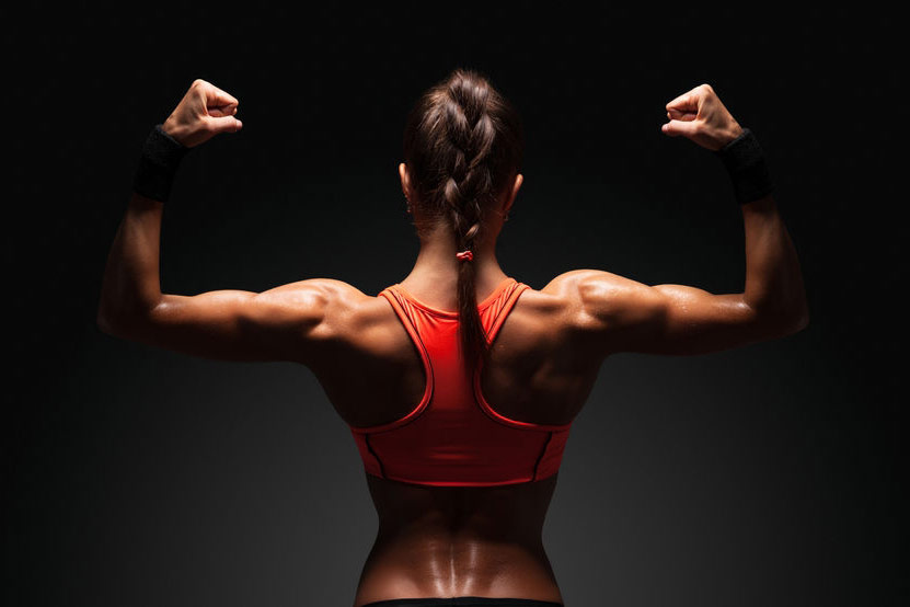 young woman flexing her shoulders and arms showing off her good muscles