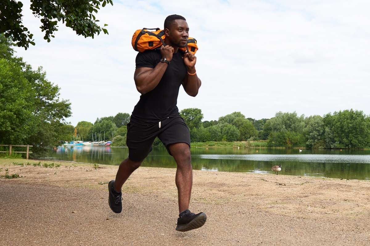 young man carrying an orange Mirafit sandbag on his shoulders whilst running around a lake