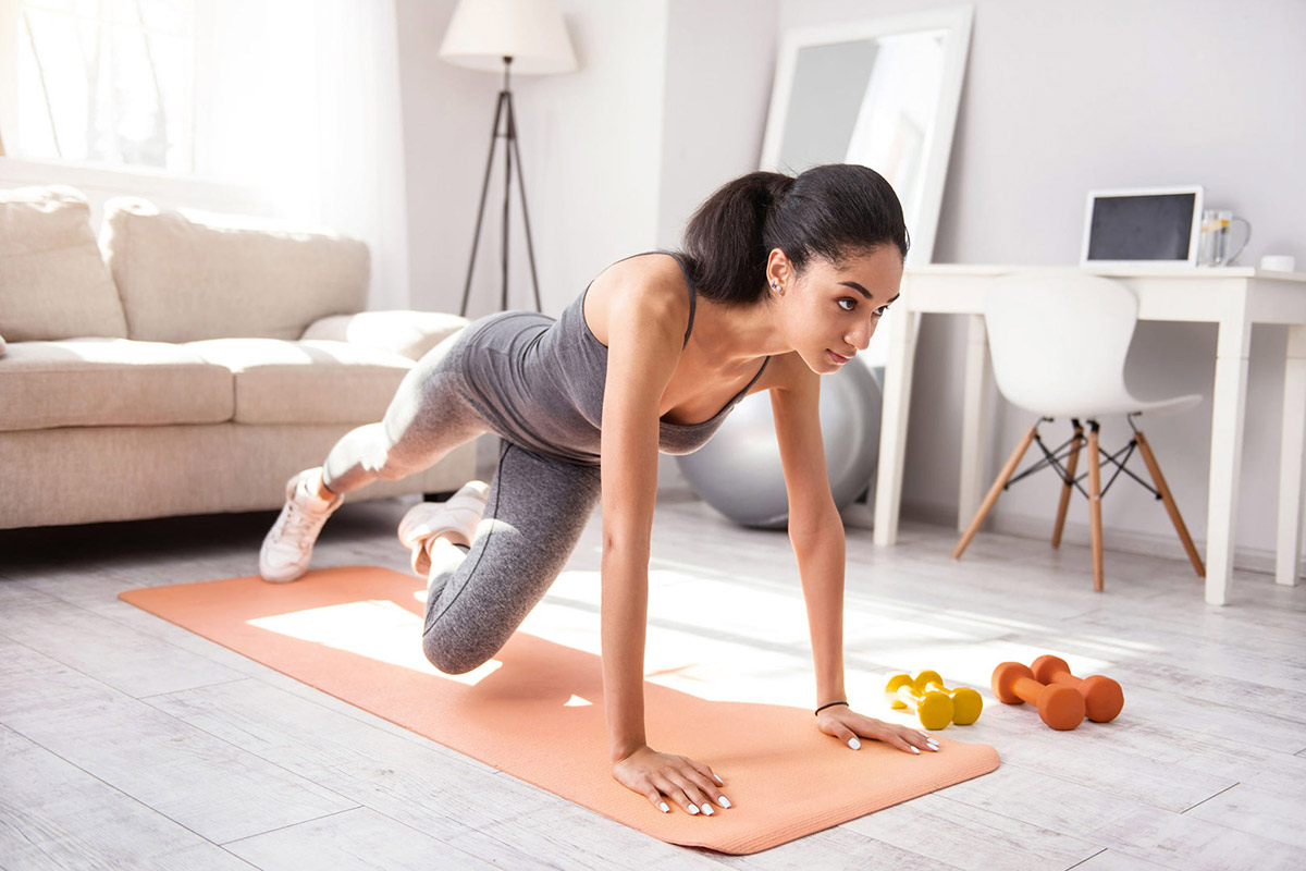 young woman doing planks while alternating legs in her living room