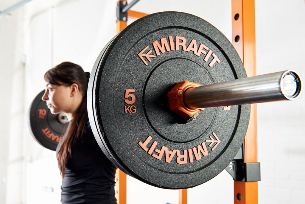 fitness expert using mirafit barbell and bumper plates