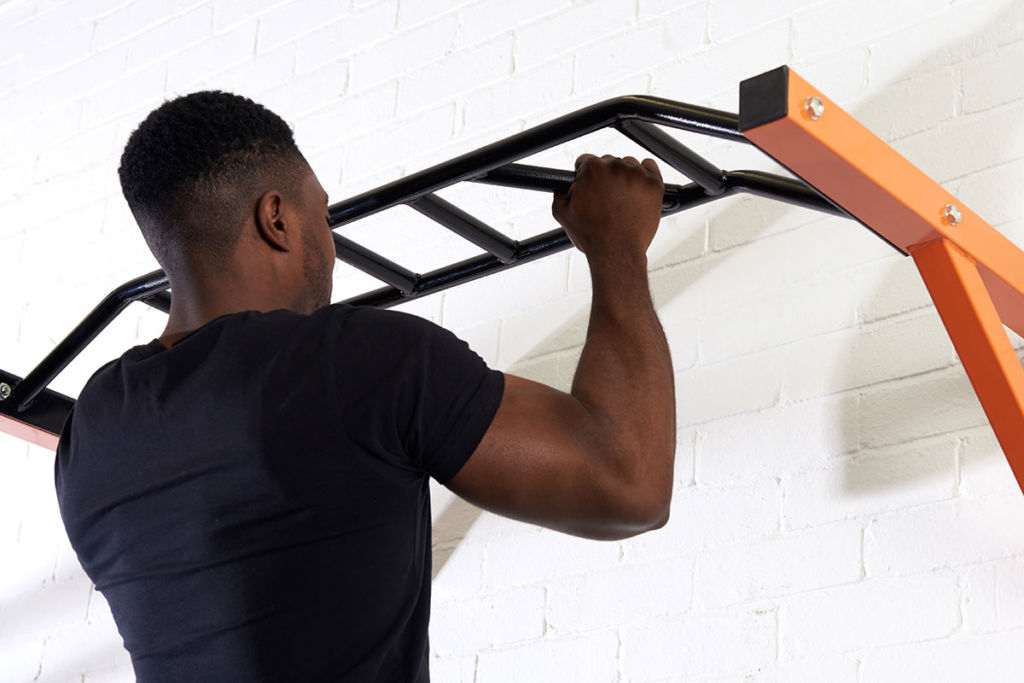 mirafit fitness expert does a pull up on a multi grip bar