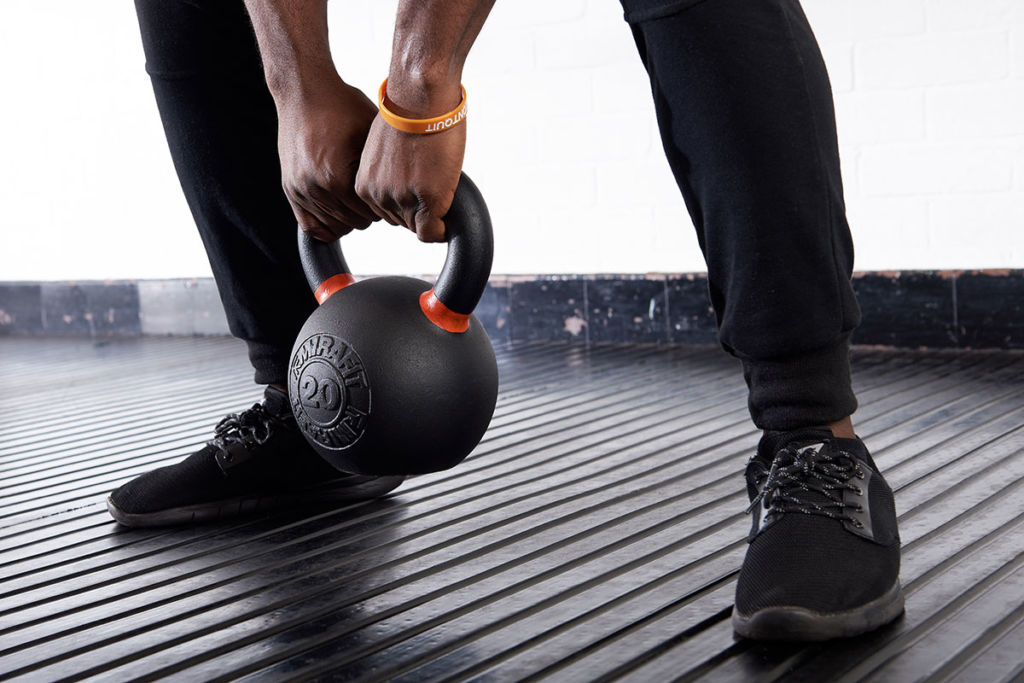 mirafit fitness expert trains with a cast iron kettlebell