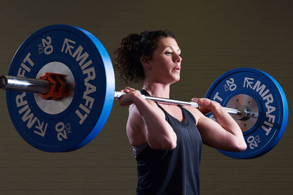 crossfit coach does a clean and jerk with mirafit barbell