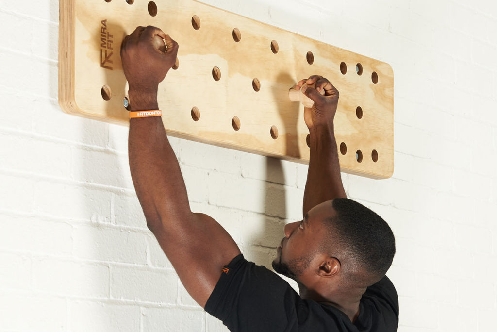 fitness expert uses a mirafit peg board to hang