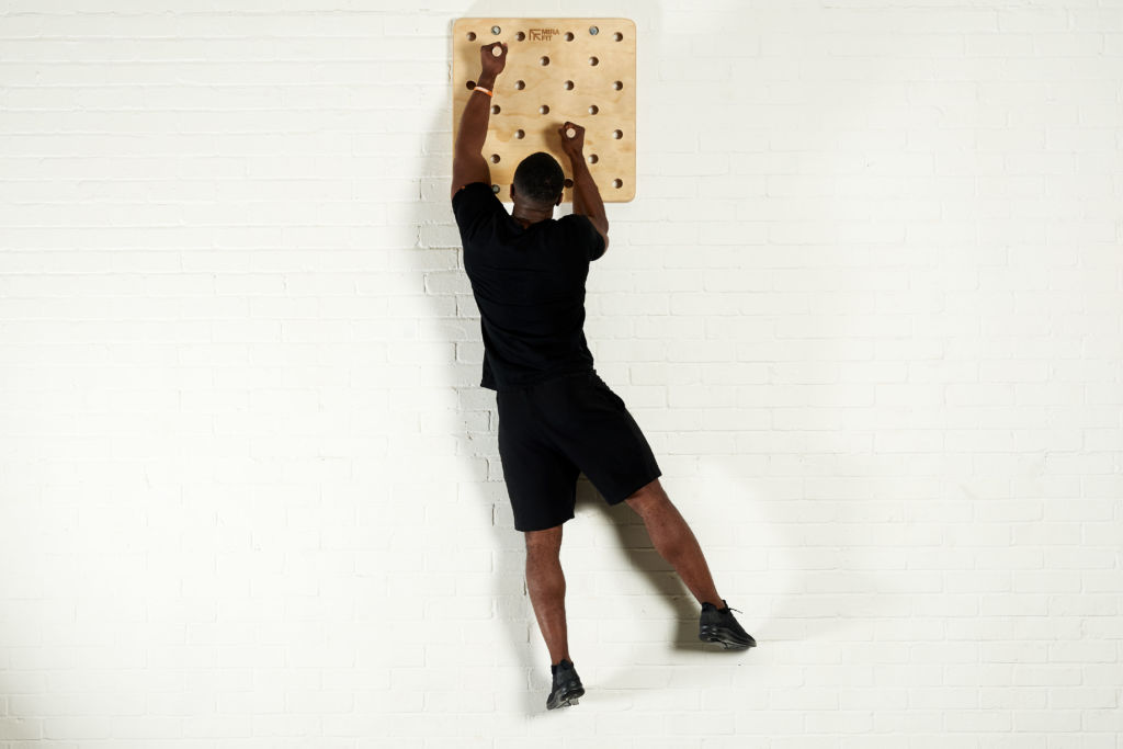 fitness expert uses a mirafit peg board to climb vertically