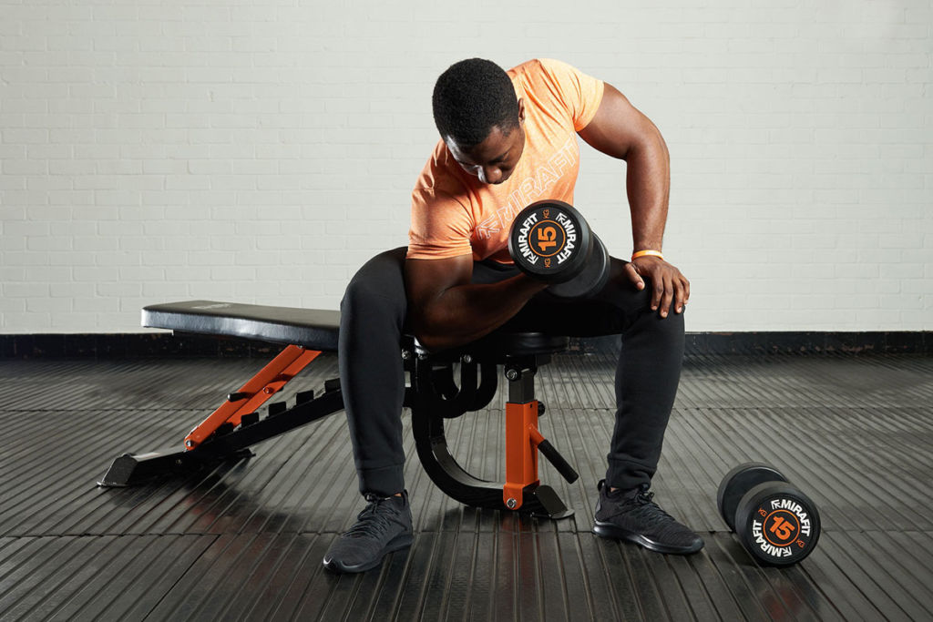 fitness expert on a mirafit weight bench doing concentration curls