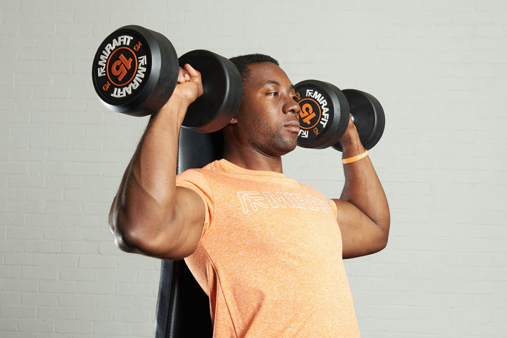 fitness expert on a mirafit weight bench doing dumbbell shoulder press