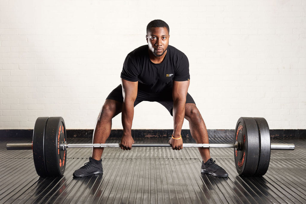 fitness expert performs a sumo deadlift using mirafit gym equipment