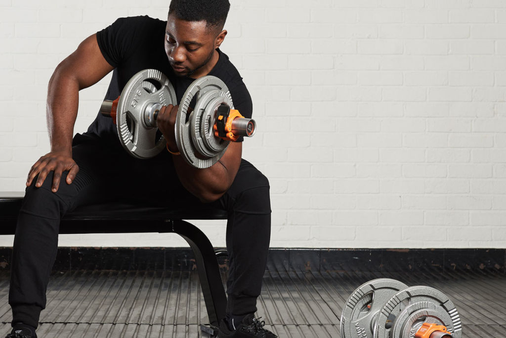 fitness expert uses mirafit dumbbells and weight bench to do concentration curls