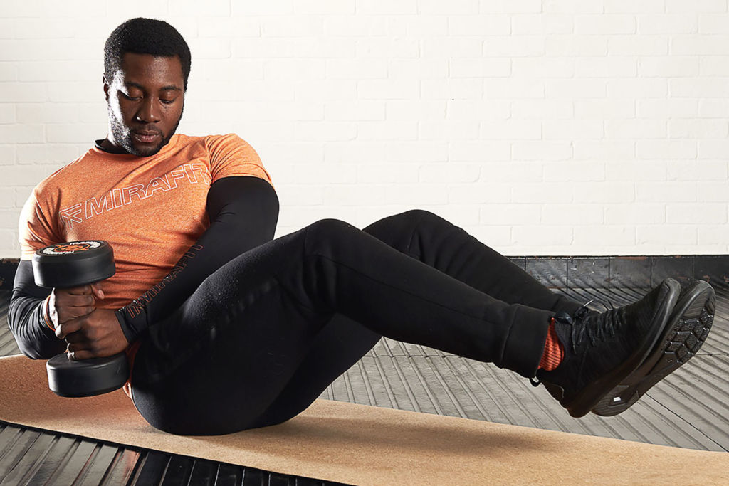 fitness expert using a mirafit dumbbell for ab exercises