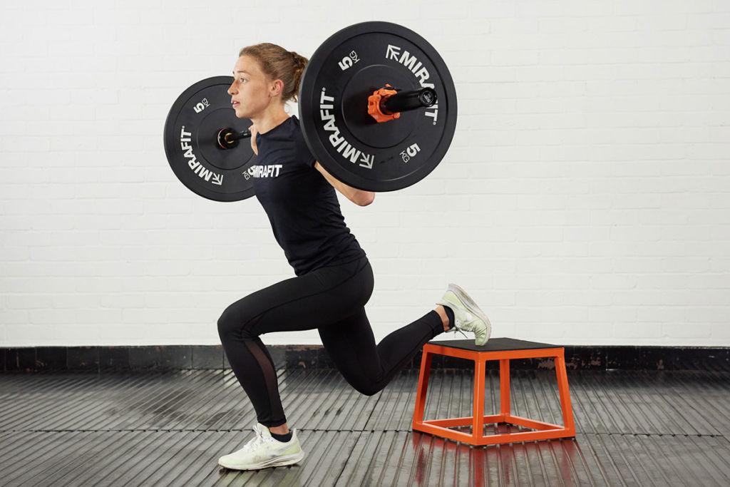 Mirafit ambassador Becky Hair doing a single leg squat on a plyo box holding an olympic barbell