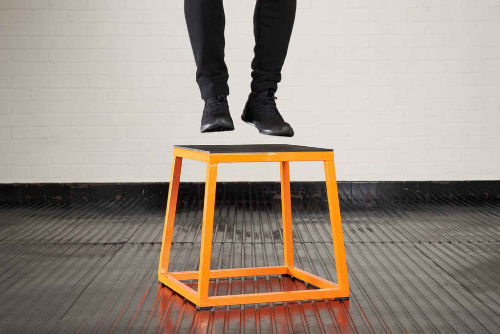 Man doing a box jump on a mirafit plyo box